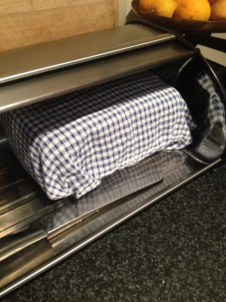 Homemade bread wrapped in a teatowel and stored in the bread tin.