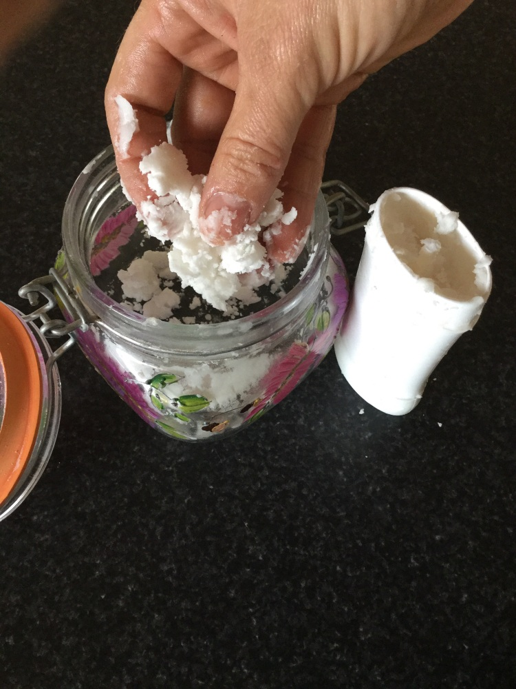 Stuffing my homemade deodorant mixture into my empty stick deodorant canister.