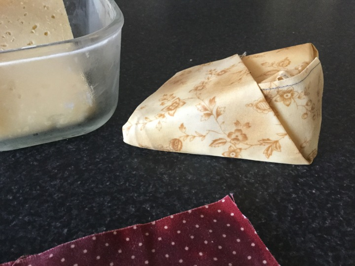 Homemade beeswax wrap wrapping parmessan cheese.
